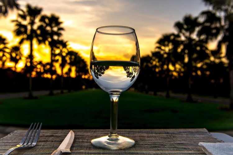 Sunset Focus On Foreground Wineglass Food And Drink Close-up Outdoors No People Wine Alcohol Nature Half Full Day Sky Kris Slater EyeEm Best Shots EyeEm Grass Reflection Wine Not