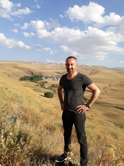 Portrait of man smiling while standing on landscape against sky