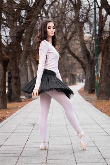 Side view of ballerina dancing on footpath