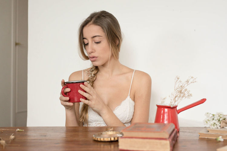 Woman looking in mug while sitting at table