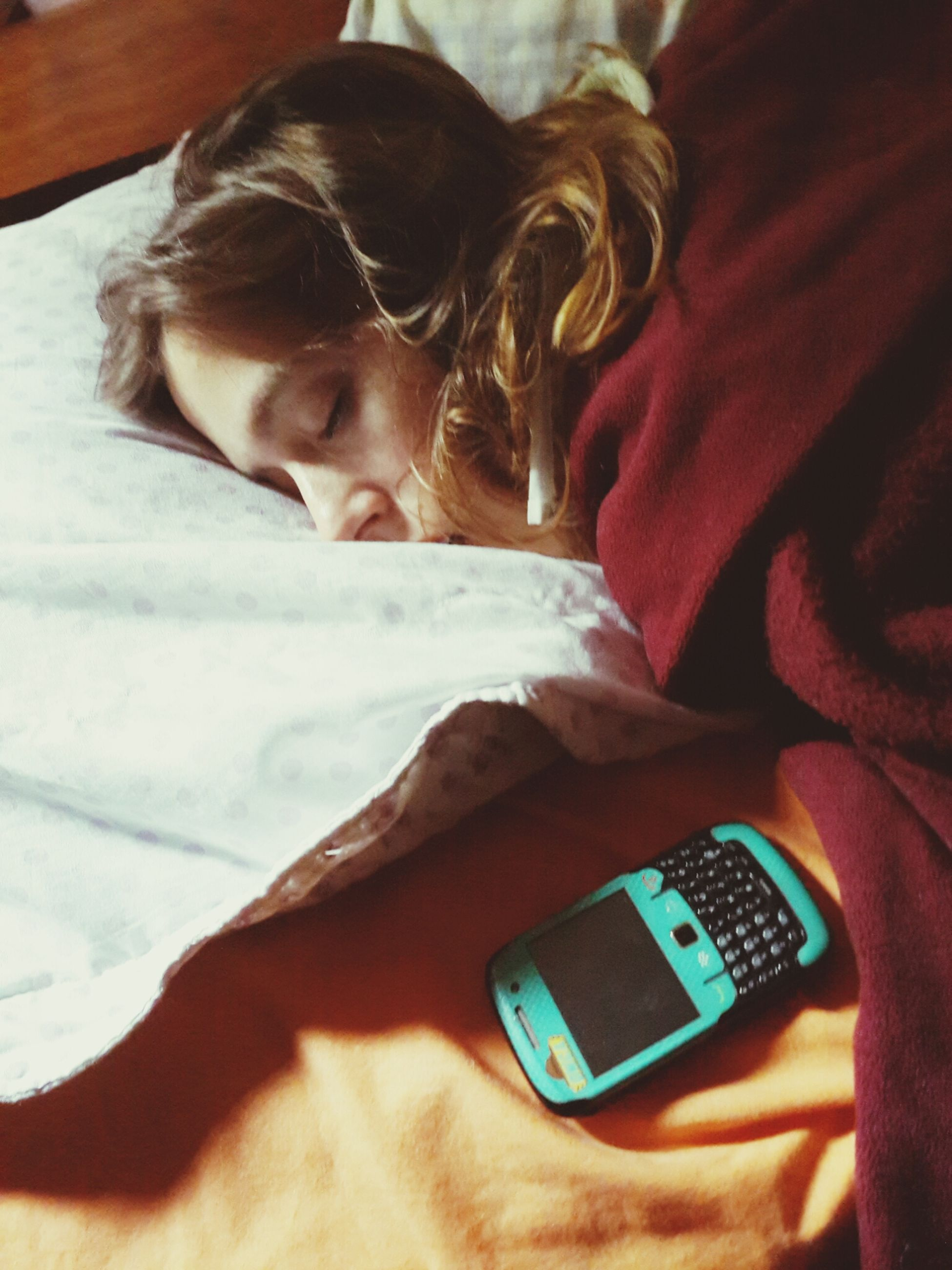 indoors, lifestyles, leisure activity, person, wireless technology, technology, casual clothing, high angle view, home interior, headshot, close-up, communication, holding, connection, bed, relaxation, young adult, mobile phone