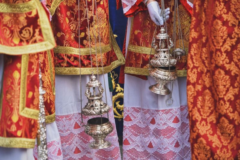 Midsection of priests holding censer during procession