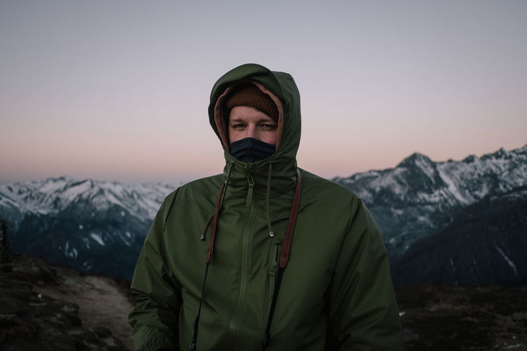 Portrait of man standing against mountain during winter
