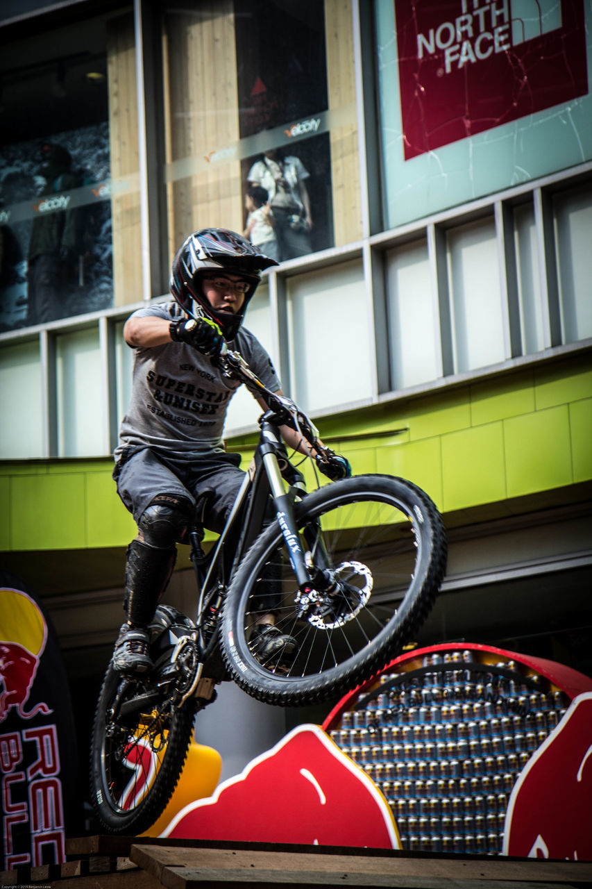 real people, one person, bicycle, land vehicle, transportation, mode of transport, helmet, building exterior, architecture, built structure, lifestyles, full length, day, outdoors, leisure activity, headwear, men, cycling helmet, young adult