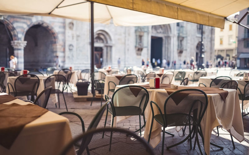 Outdoor restaurant in Milano, Italy. Incidental People Unrecognizable People Restaurant Cafe Chair Seat Table Sidewalk Cafe Group Of People Outdoors Absence Sunlight Empty Building Exterior Milan Italy Summer Focus On Foreground Day