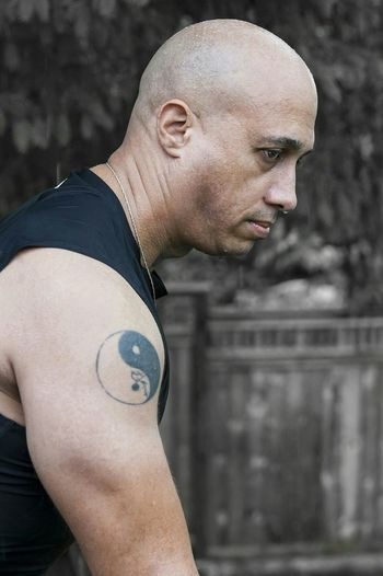 Side view of shaved head man with yin yang symbol tattoo