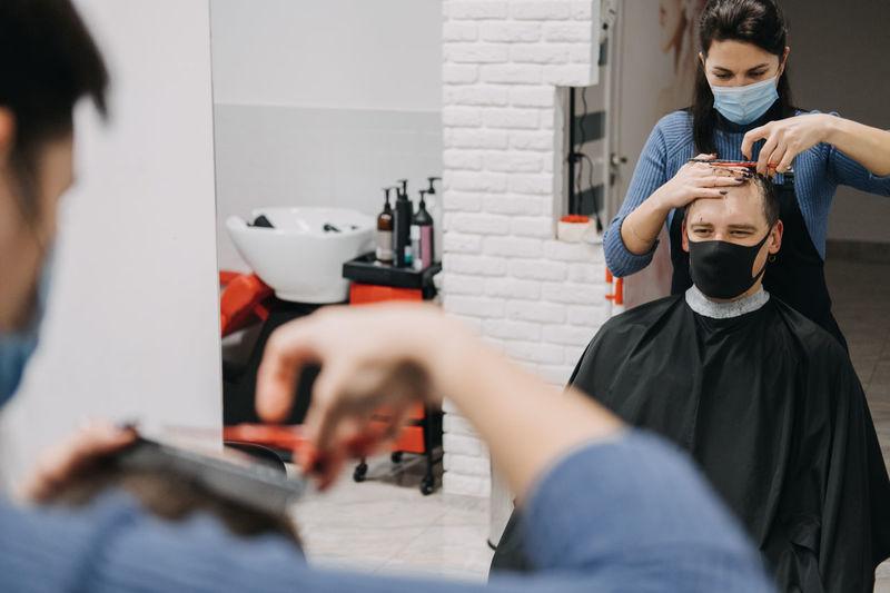 Female barber wearing mask cutting hair of man at salon