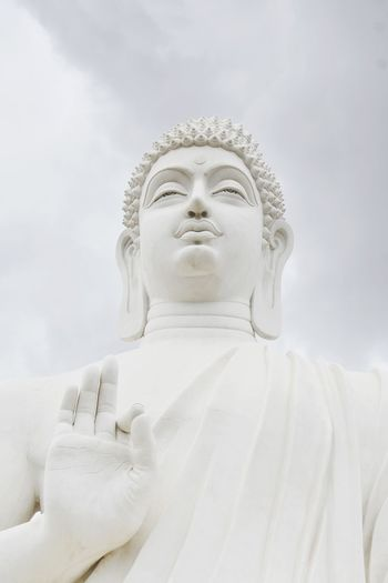 Low angle view of statue of buddha against cloudy sky