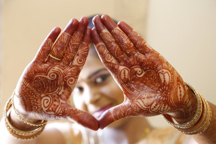 Close-up of woman hands in henna tatoos