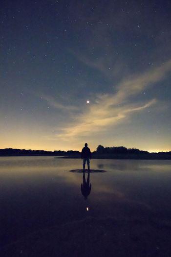 Silhouette man standing amidst lake against dusk