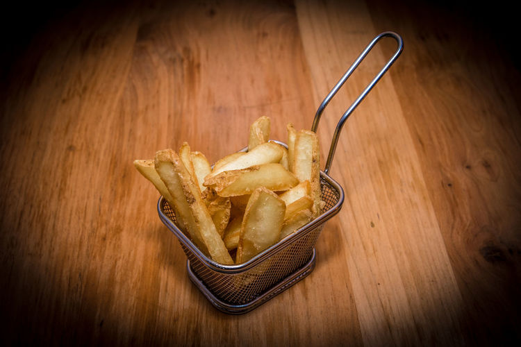 Close up of delicious french fries on steel food basket Food And Drink Food Wood - Material Indoors  No People Freshness Table Close-up Vignette Potato Fried Ready-to-eat Kitchen Utensil Prepared Potato Unhealthy Eating Bowl French Fries Snack High Angle View Wood Wood Grain Comfort Food