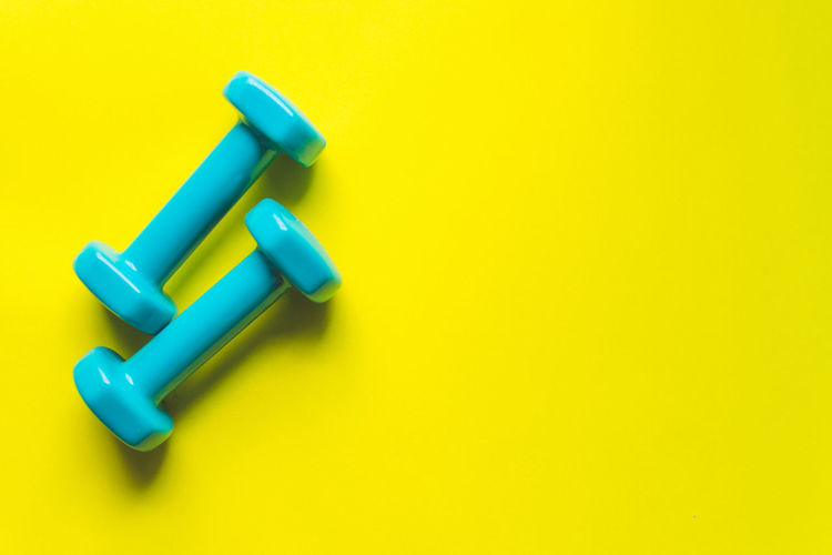 Fitness Equipment Dumbbell Gym Yellow Still Life Studio Shot No People Indoors  Blue Close-up High Angle View Copy Space Colored Background Vibrant Color Multi Colored Simplicity Cut Out Two Objects Green Color Plastic Pen Wood - Material Felt Tip Pen