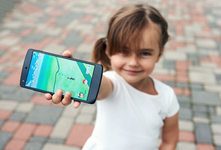 Little girl playing a Pokemon Go game outdoors. Pokemon Go is a popular virtual reality game for mobile devices. The game allows players to capture, battle, and train virtual creatures, called Pokemon, who appear on device screens as though in the real world. 5 Years Old Alone Beautiful Caucasian Cell Cellphone Child Childhood Daughter Device Editorial  Entertainment Game Illustrative Little Girl Mobile Phone Outdoors Phone Pokemon Go Selective Focus Small Girl Smartphone Smiling Summer Technology