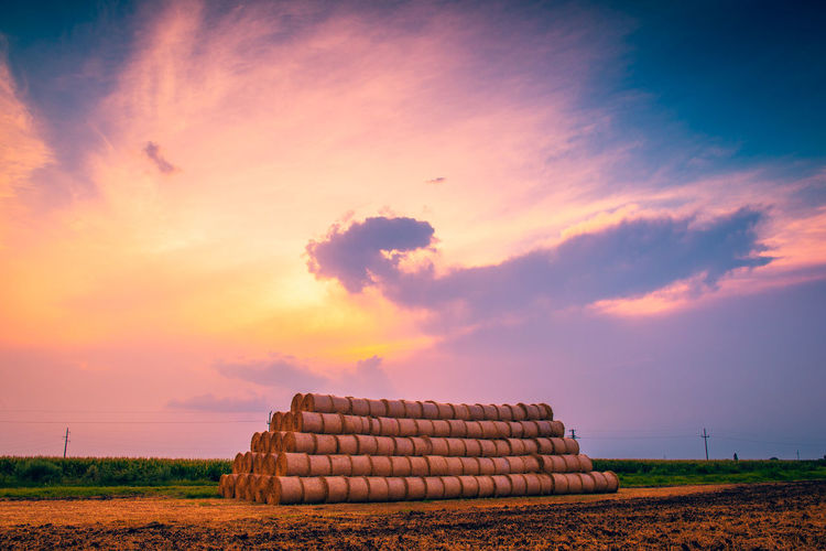 Stack of hay bales on field against sky during sunset