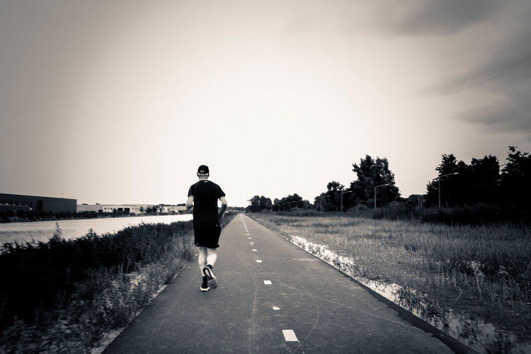 Rear View Of Man Jogging On Road Against Clear Sky
