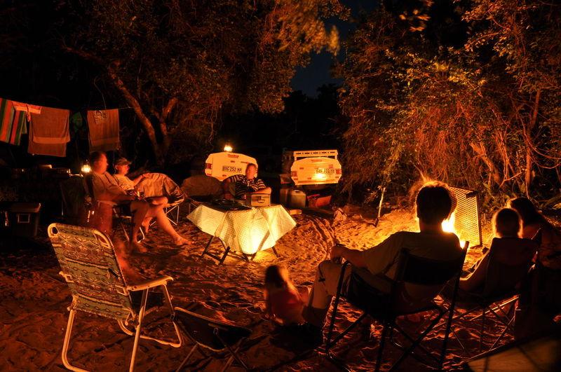 People on illuminated chair at night