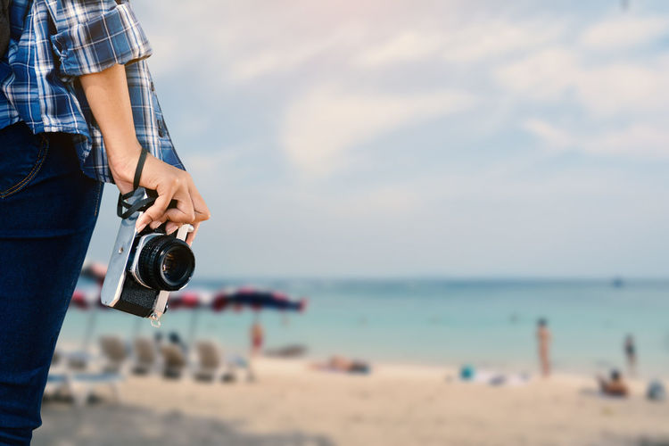 Midsection of woman holding camera on beach