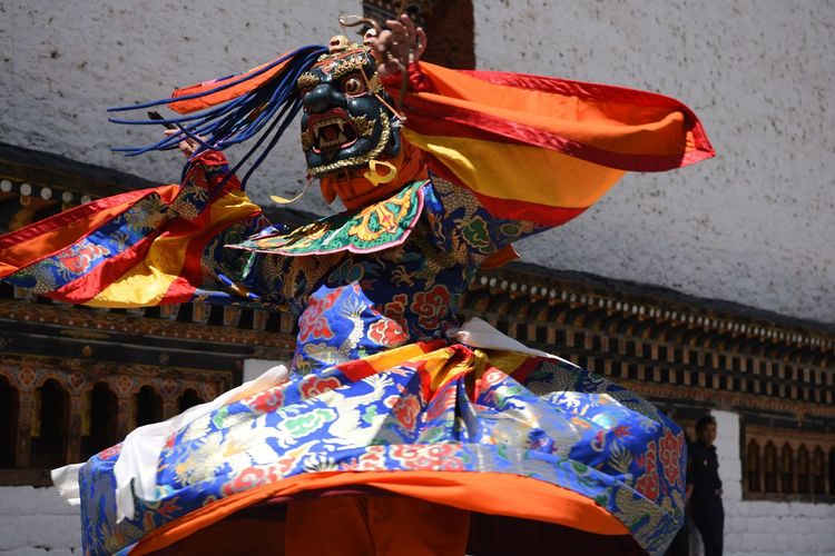Low angle view of person wearing colorful costume while dancing against wall