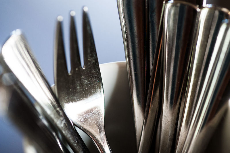 Close-up of silverware in container