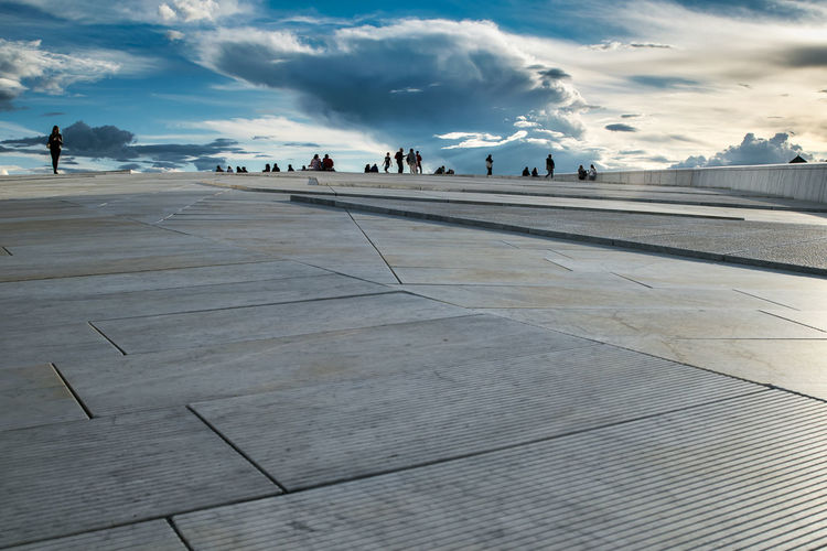 Surface Level View Of People At Oslo Opera House Against Sky