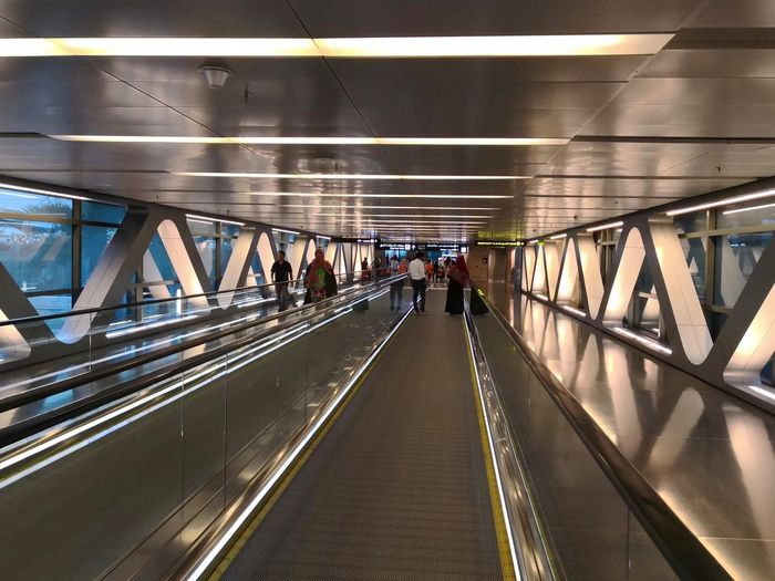 Hamad International Airport Doha Qatar Hamad International Airport City Illuminated Futuristic Modern Full Length Journey Architecture Built Structure Travel Moving Walkway  Airport Terminal Airport Departure Area Passenger Boarding Bridge Arrival Departure Board