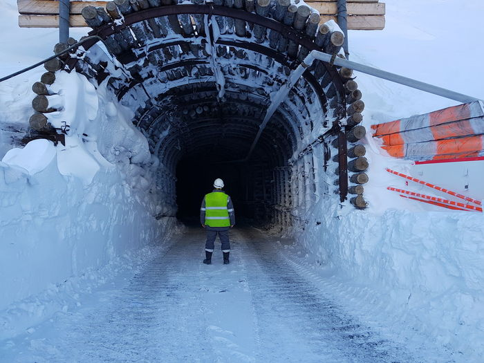 Rear view of manual worker standing in tunnel during winter