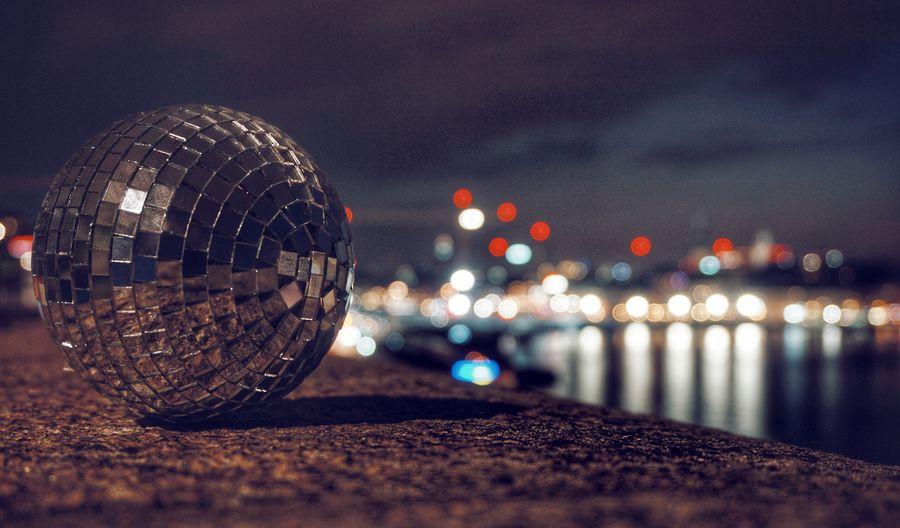 Illuminated disco ball at night