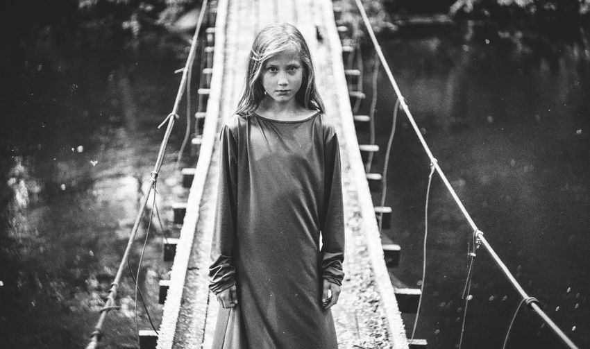 Portrait of girl standing on rope bridge