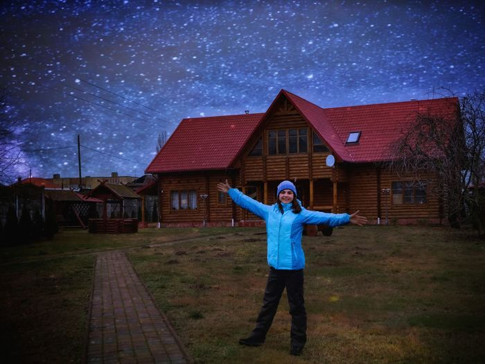 Portrait of teenage girl standing with arms outstretched against house at night