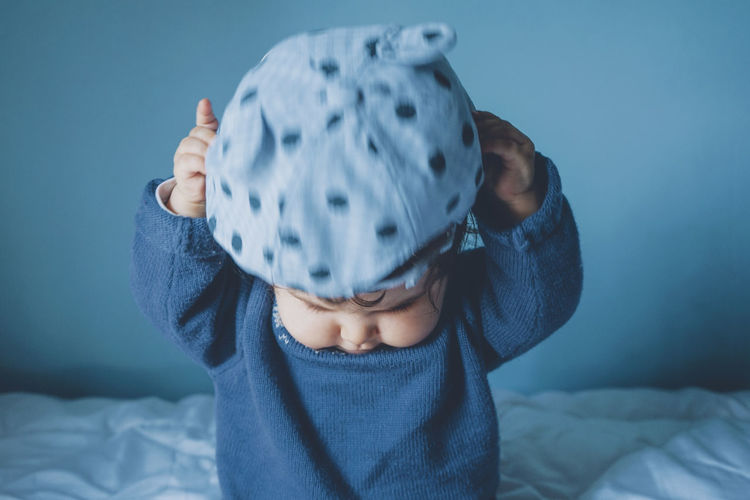 Portrait of cute boy covering face on bed