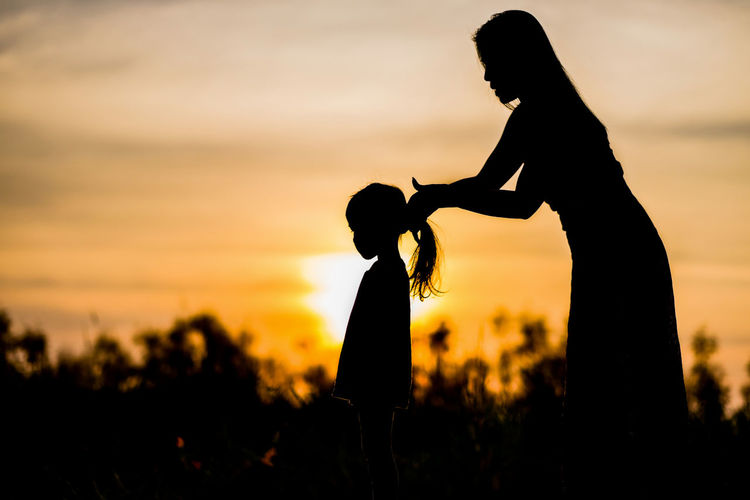 Silhouette of mother and daughter on field at sunset