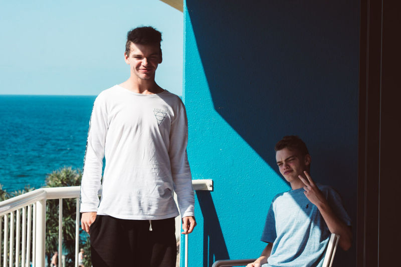 Portrait of male friends at balcony against sea