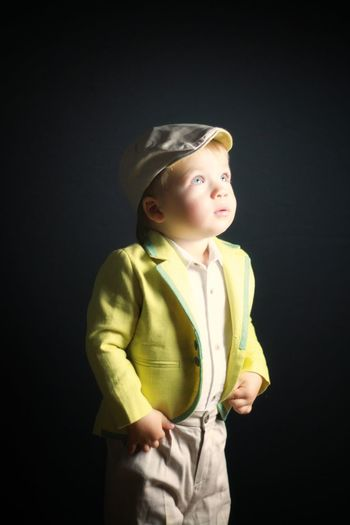 Boy looking away while standing against black background