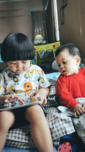 Baby boy sitting with sister using digital tablet on bed