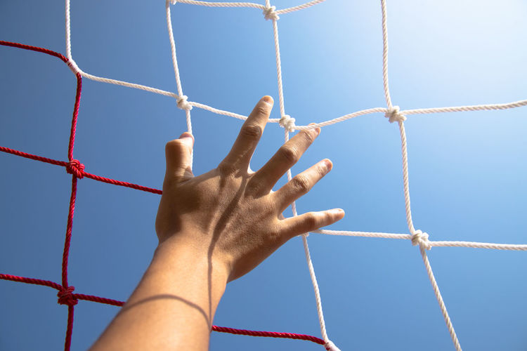 Cropped hand touching soccer net against clear sky