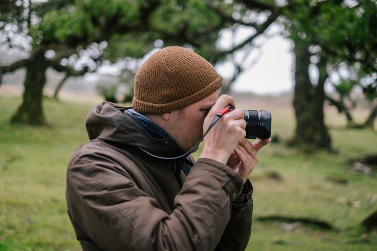 Midsection of man photographing with camera on field