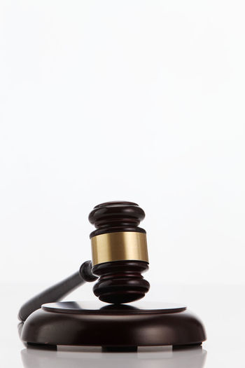 Close-Up Of Gavel On Wood Against White Background