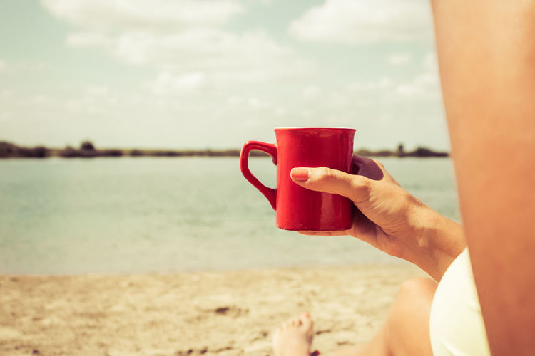 Close-up of woman drinking coffee while relaxing on sandy beach in summer day. copy space.