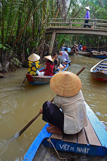 Mobility In Mega Cities Asian Culture Bridge Canoe Hat Lifestyles Mekong Delta Mekong River Modeoftransport Real People Rowing Tradition Woman Women Transportation River Asian Style Conical Hat Mode Of Transport Water Nature