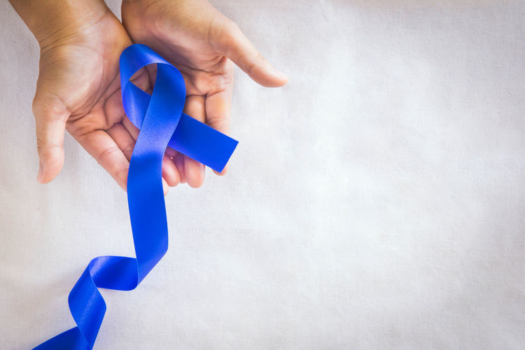 Close-up of hand holding paper against blue background