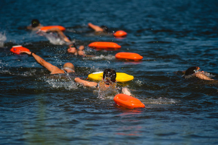 Rear view of people swimming in sea