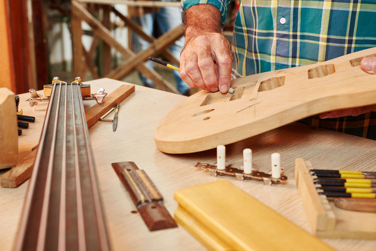 Midsection of man working on guitar over table