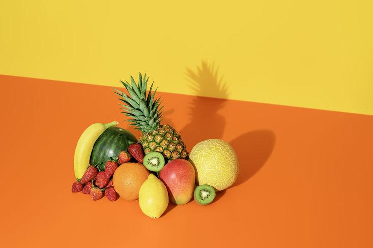 Fruits on table against orange background