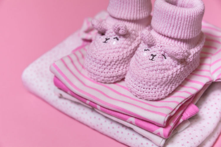 Close-up of baby booties and clothing against pink background