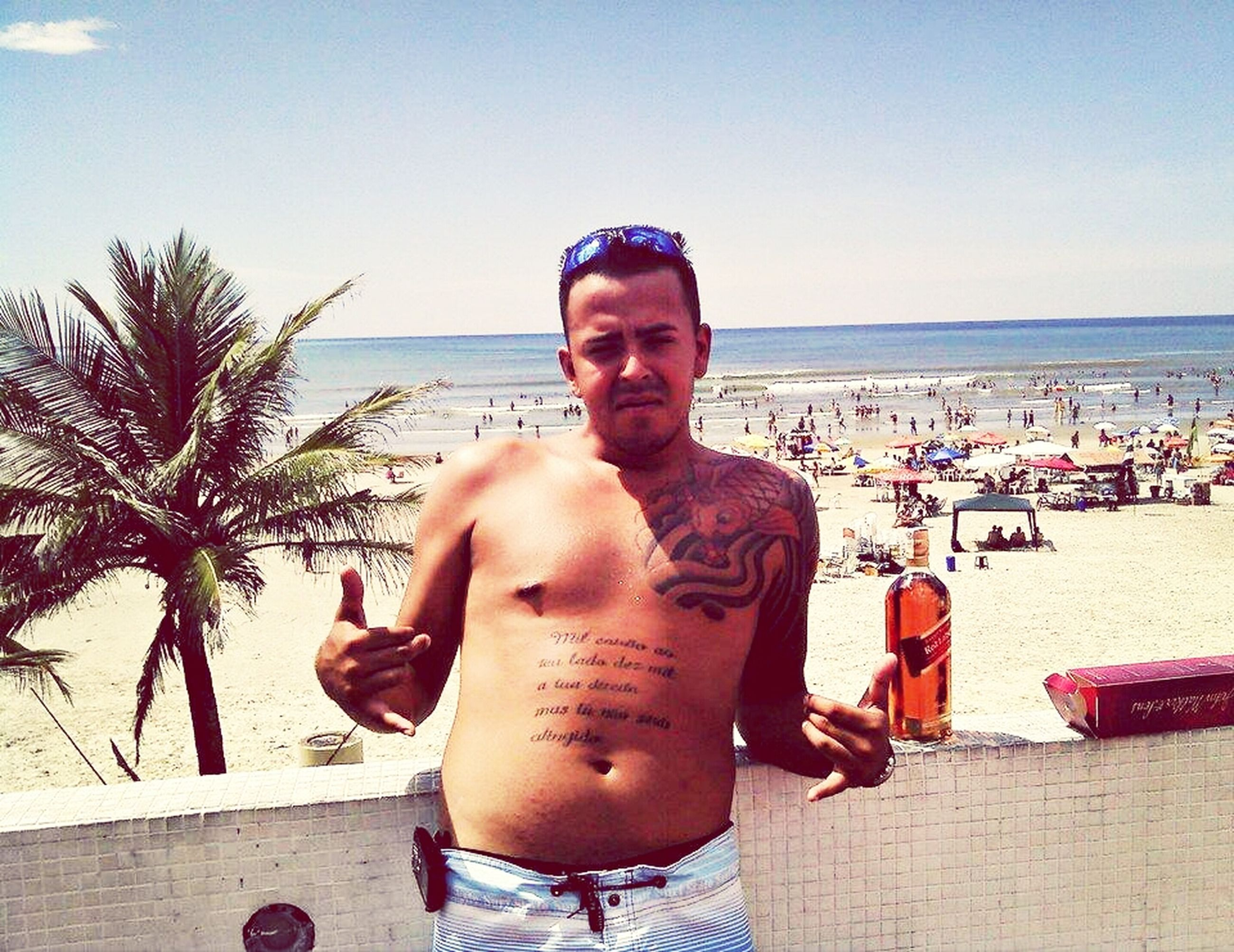 lifestyles, leisure activity, person, beach, sunglasses, sea, holding, sitting, food and drink, looking at camera, water, young men, portrait, young adult, sky, waist up, front view, smiling
