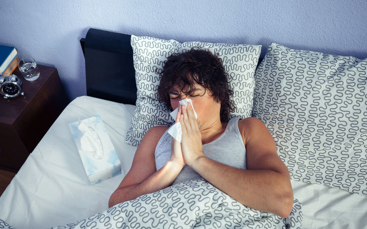 Young man sneezing and covering nose with tissue lying on bed. Sickness and healthcare concept. Bed Horizontal Lying Man Medicine Tissue Unhappy Allergy Bedroom Cold Fever Flu Grippe Headache Heat Illness Influenza Male Nasal One Person Real People Sick Sickness Sneezing Temperature