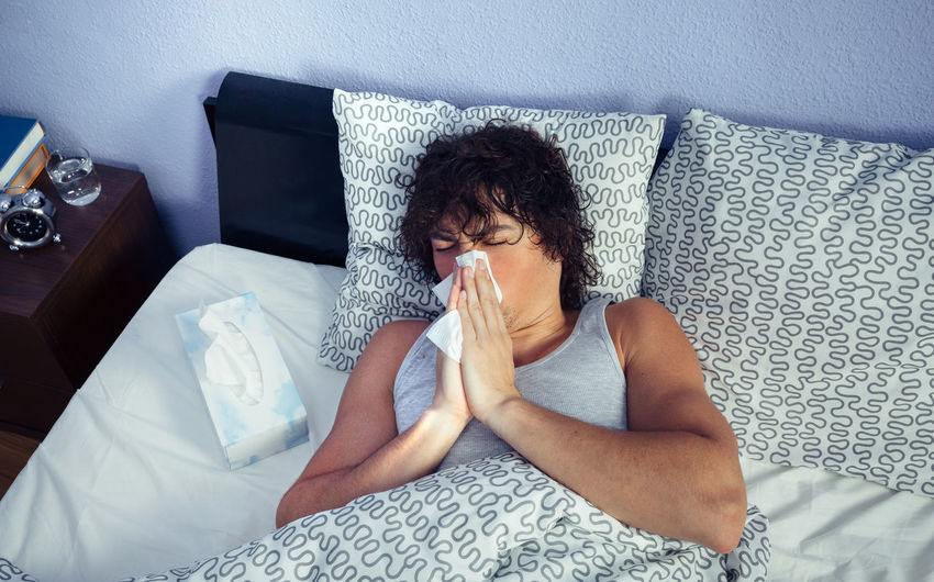 High angle view of young man with flu on bed at home