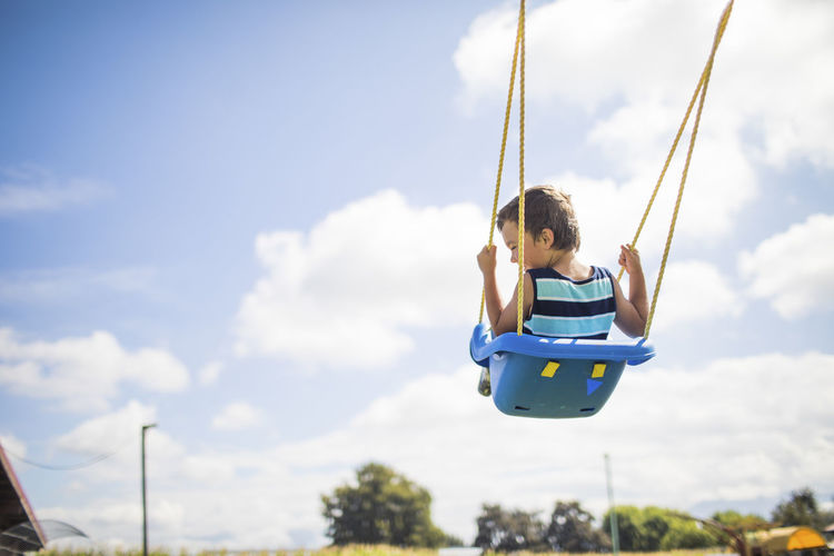 Low angle view of swing in playground against sky
