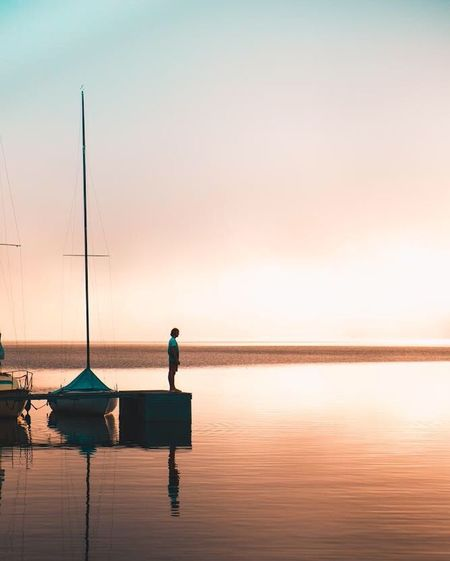 Reflection Sunset Sea Tranquility Water One Person Nature Scenics One Man Only Beauty In Nature Clear Sky Standing Idyllic Sky Tranquil Scene Silhouette Full Length Outdoors People Horizon Over Water