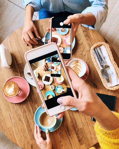 Coffee mood. Woman's taking photos of coffee and deserts on mobile phones Top View Of Food Using Phone Colorful Food And Drink Blogger Coffee - Drink Friends Food And Drink Hand Human Hand Table Human Body Part Food High Angle View Real People Drink Eating Lifestyles Directly Above Two People Wireless Technology